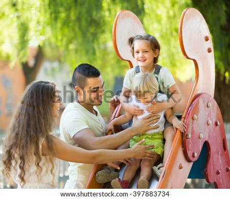 Happy young parents with two daughters playing at children's slide. Focus on girl