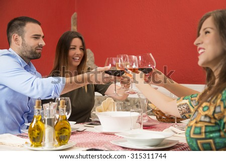 Happy young people celebrating. They are toasting with wine at restaurant during a lunch. - stock photo