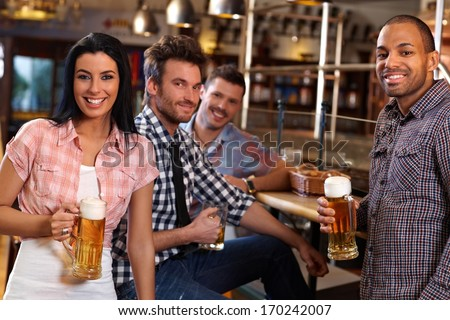 Happy young people drinking beer in pub, smiling.