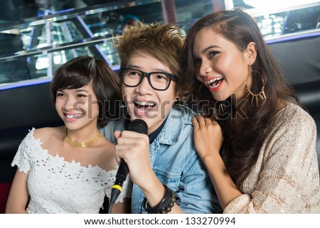 Happy young people enjoying themselves singing karaoke in the bar - stock photo