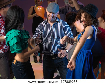 happy, young people flirting and dancing on the dancefloor, in a night club