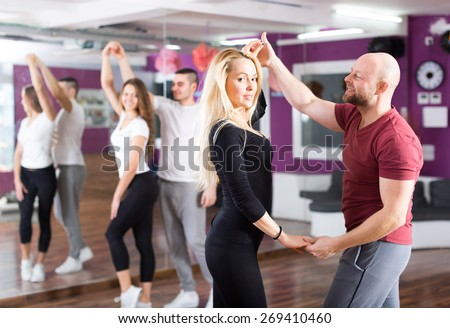 Happy young people having dancing class in classroom - stock photo