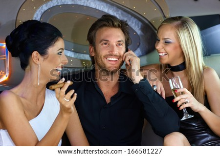 Happy young people having fun in luxury car, drinking, smoking cigar.