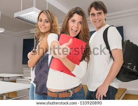 Happy young people in a classroom - stock photo