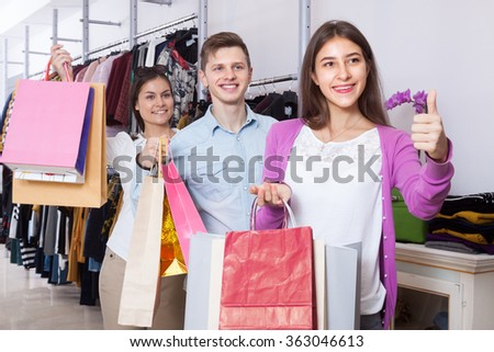 Happy young people in a clothing store with shopping bags