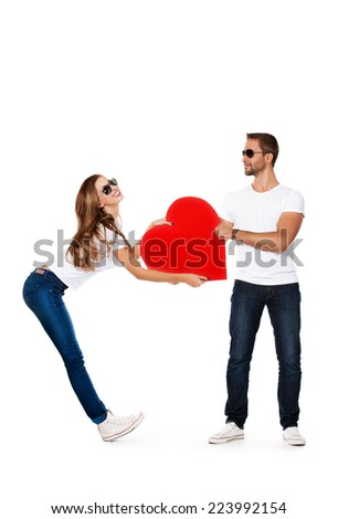 Happy young people in love posing with big red hearts. Isolated over white.