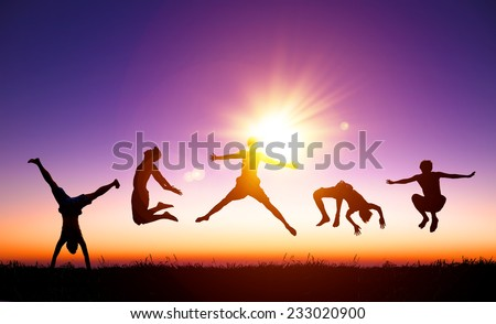 happy young people jumping on the hill with sunlight background - stock photo