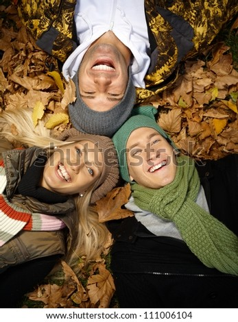 Happy young people laying among leaves in autumn park, laughing, enjoying themselves. - stock photo