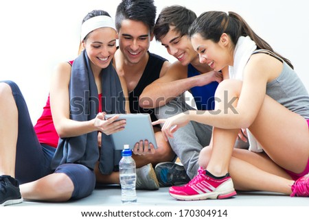 Happy young people looking at digital table in the gym after making exercise - stock photo