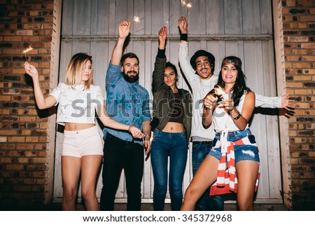 Happy young people out at night, celebrating with sparklers. Young friends having a party outdoors. - stock photo