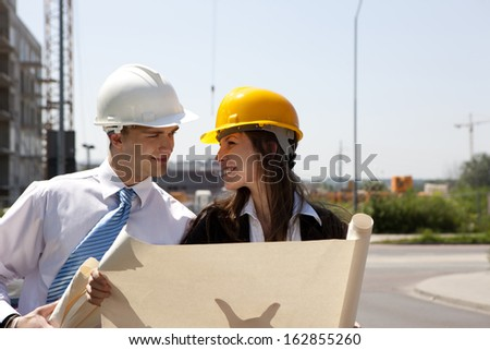 Happy young people planing future house on construction site. - stock photo
