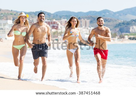 Happy young people running on the beach near the sea. Focus on the right couple
