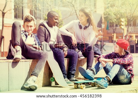 Happy young  people spending time together and talking in sunny day - stock photo