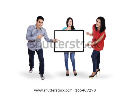 Happy young people standing together and holding a blank placard for your text - stock photo