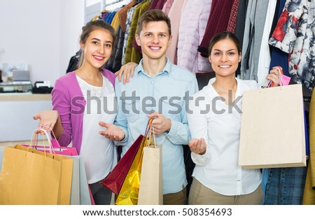 Happy young people with purchases in apparel shop