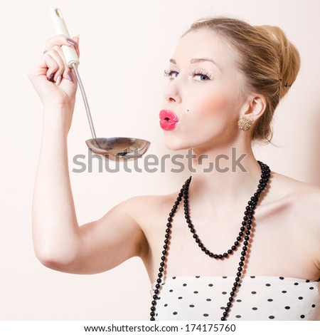 Happy young pinup woman with ladle blowing and looking at camera - stock photo