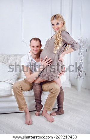 Happy young pregnant couple embrace each other on a sofa in white living room. - stock photo