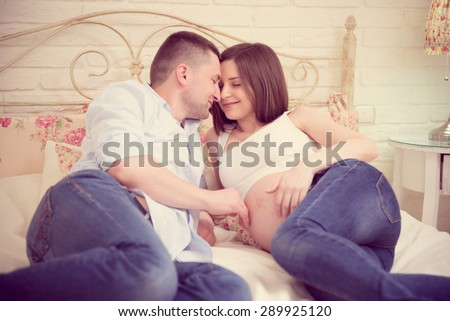 Happy young pregnant couple in bedroom at home - stock photo