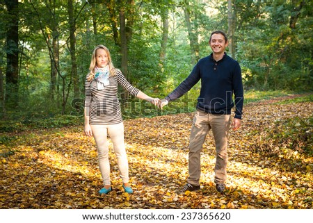 Happy young pregnant couple in love holding hands on the walk in autumn nature - stock photo
