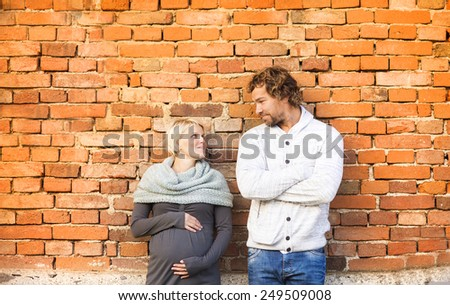 Happy young pregnant couple standing outside an old brick house. - stock photo