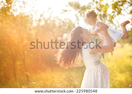 Happy young pregnant mother and her little daughter have fun in summer nature - stock photo