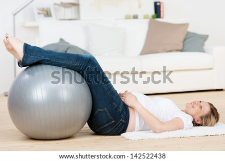 Happy young pregnant woman exercising with Pilates while lying on floor at home