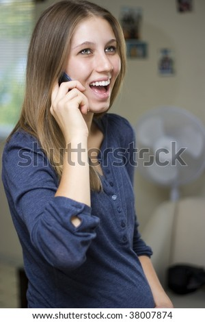 Happy young pregnant woman laughs while talking on the phone.