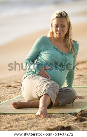 Happy young pregnant woman sitting on mat at Florida beach