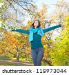 Happy young pretty woman at the autumn colored park. - stock photo