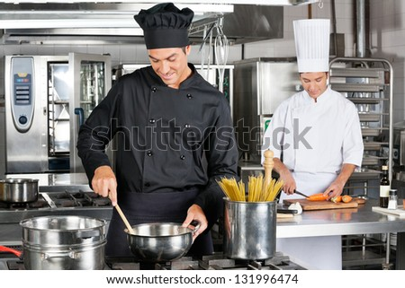Happy young professional chefs preparing spaghetti in commercial kitchen