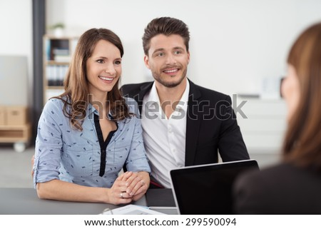 Happy Young Professional Couple Talking to a Real Estate Agent Inside the Office - stock photo