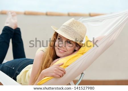 Happy young redhead woman daydreaming in hammock - stock photo