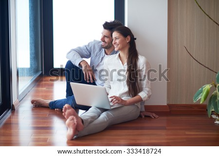 happy young relaxed  couple working on laptop computer at modern home interior - stock photo