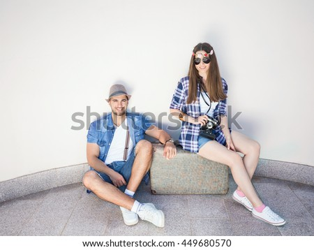 Happy young retro styled hippie couple with an old-fashioned suitcase in front of the white curved wall. They wear matching outfits. Young man is sitting on the floor and looking at camera - stock photo