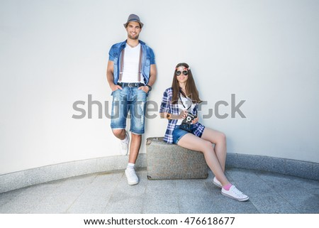 Happy young retro styled hippie couple with an old-fashioned suitcase in front of the white curved wall. They wear matching outfits.