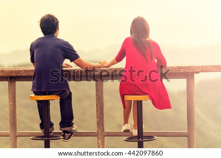 Happy young romantic couple looking at a beautiful landscape scene. Traveling and Relax Concept. - stock photo