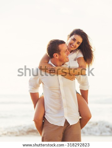 Happy Young Romantic Couple Playing and Having Fun on the Beach