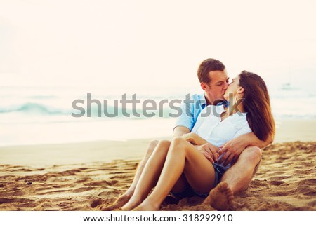 Happy Young Romantic Couple Relaxing on the Beach. Kissing and Watching the Sunset