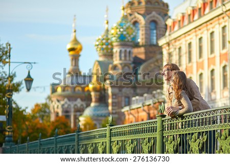 Happy young romantic couple walking together in St. Petersburg, Russia on a warm sunny autumn day near the Church of the savior on Blood