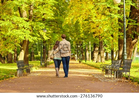 Happy young romantic couple walking together in St. Petersburg, Russia on a warm sunny autumn day