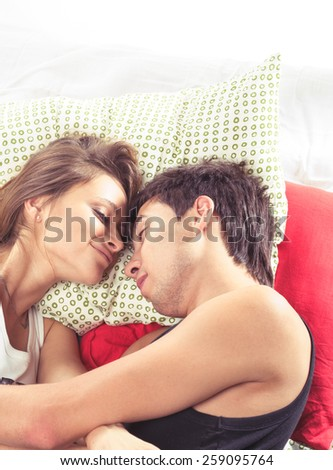 Happy young romantic mixed couple in bed  - stock photo
