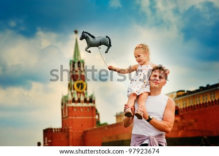 happy young russian family on on Red Square against the background of the Moscow Kremlin - stock photo