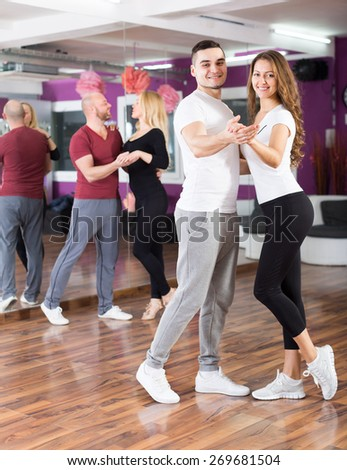 Happy young russian people having dancing class indoors - stock photo