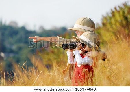 Happy young safari adventure children playing outdoors in the grass with binoculars and exploring together as brother and sister. - stock photo