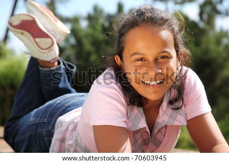 Happy young school girl relaxing in the bright sunshine