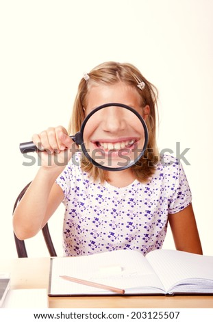 happy young school girl sit with a magnifying glass in hand and write homework/happy young school girl