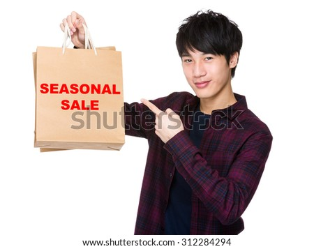 Happy young shopper with finger point to paper bag for showing pharse of seasonal sale