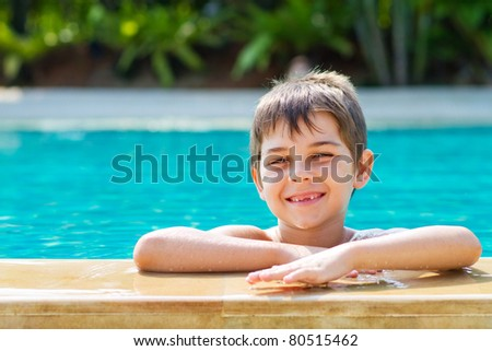 Happy young smiling boy in the pool - stock photo