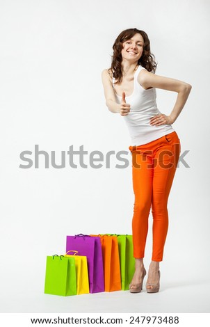 Happy young smiling brunette in orange pants with shopping bags showing thumbs up, full length portrait on neutral background - stock photo