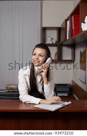 Happy young smiling businesswoman sitting at the table in office meeting room, talking on phone and writing